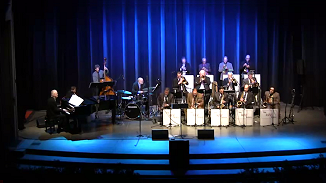 Reno Jazz Orchestra title above a photo of the Orchestra playing live on stage